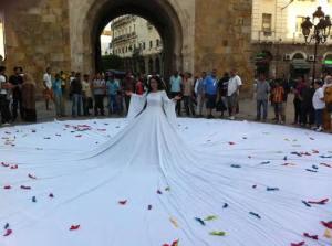 """Presa dalla pagina Facebook di T. Lamri: """"Raeda Saadeh, artista palestinese. L'artista, nel 2011, presso l'università Bir Zeit (Palestina) indossa un immenso abito bianco che lascia ricadere per vari metri attorno a lei, come un derviscio rotante. Il pubblico è invitato a deporre sull'abito pezzi di stoffa colorata sui quali ognuno scrive i suoi desideri, sogni... L'artista si carica delle aspirazioni e desideri del popolo""""."""