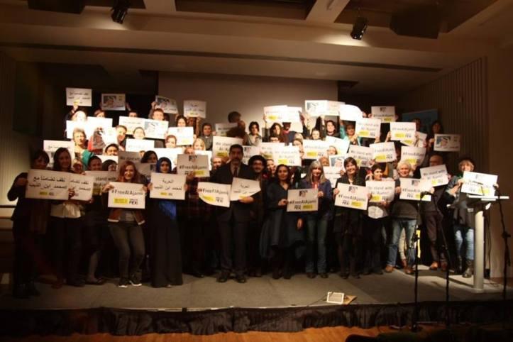 I partecipanti alla serata sorreggono cartelli che chiedono la liberazione immediata di al-Ajami